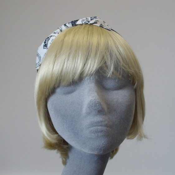 Headband with a white fabric bow with black postmark stamps.