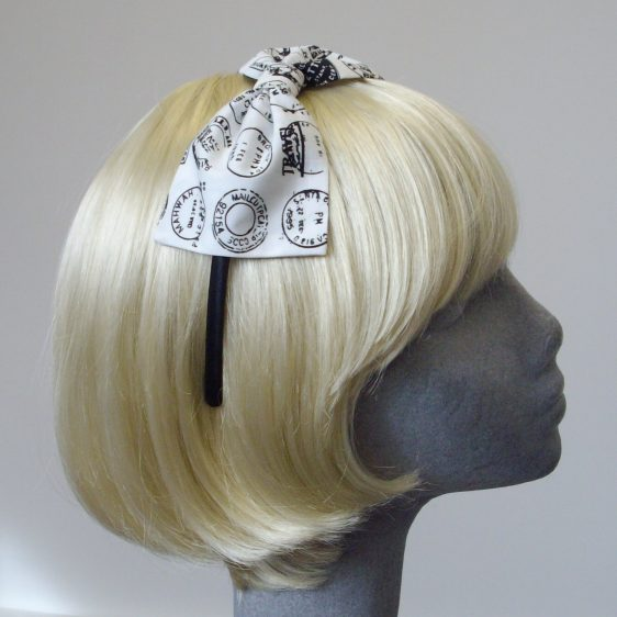 side view of a black satin headband with a white fabric bow, featuring postmarks printed in black