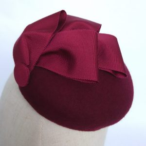 Spring wedding hat by Imogen's Imagination Showing detail on the wine red ribbon loops which decorate the top of the felt button hat.
