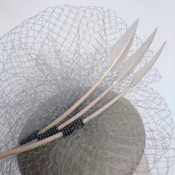 Detail of a grey hat with veiling feathers and beading