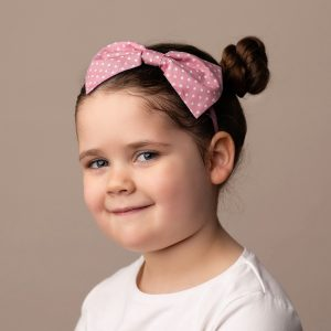 Dusky Pink Polka Dot Headband worn by a child with a bun hair style