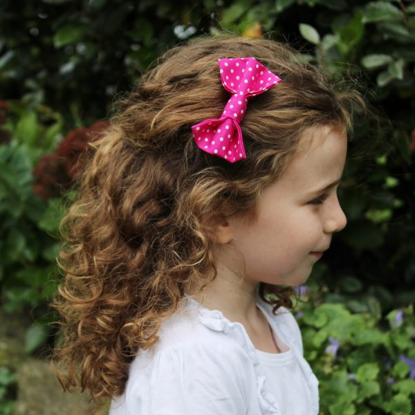 Hot Pink Polka Dot Hair Clip worn by a child with light brown curly hair