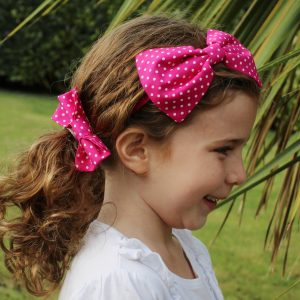Hot Pink Polka Dot Headband and Hair clip worn together by a child