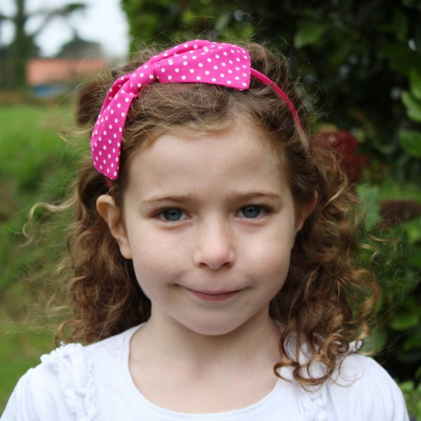 Hot Pink Polka Dot Headband worn by a child with light brown curly hair