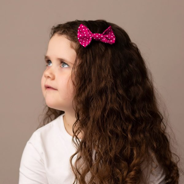Hot Pink Polka Dot Hair Clip worn by a child with a long curly hair