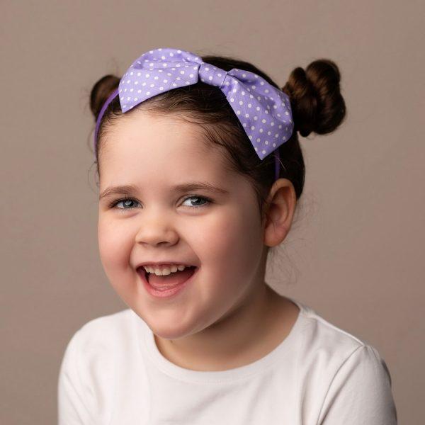 Lilac Polka Dot Headband worn by a child with a bun hair style