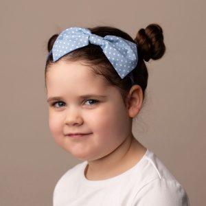 Pale Blue Polka Dot Headband worn by a child with a bun hair style