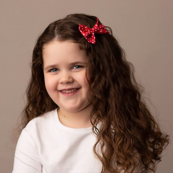 Red Polka Dot Hair Clip worn by a child with a long curly hair
