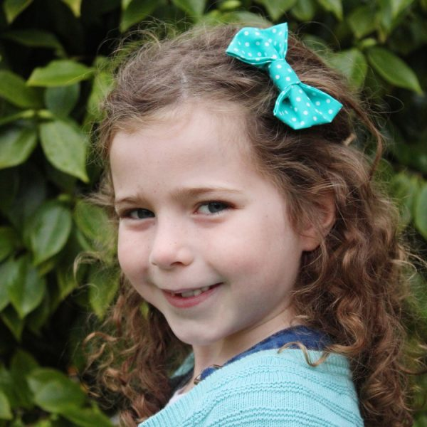 Turquoise Polka Dot Hair Clip worn by a child with light brown curly hair