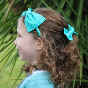 Turquoise Polka Dot Headband and Hair clip worn together by a child