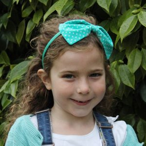 Turquoise Polka Dot Headband worn by a child with light brown curly hair