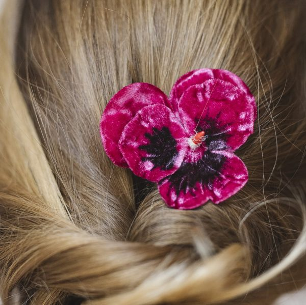 Detail image of Fuchsia Pansy Flower Hair Clip worn with ponytail