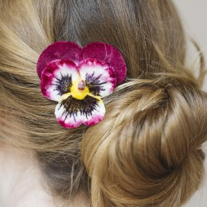 Detail Image of Magenta Pansy Flower Hair Clip worn with a low bun