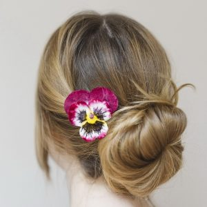 Magenta Pansy Flower Hair Clip worn with a low bun