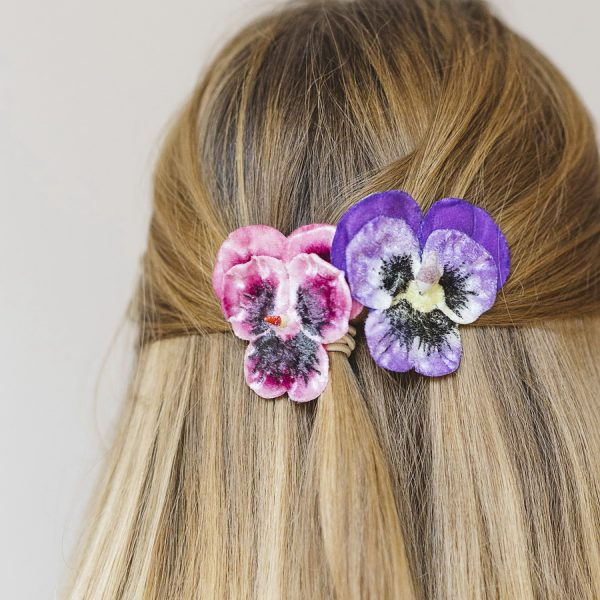 Detail image of Purple and Pink Large Pansy Flower Gift Set hair clips worn with a half ponytail