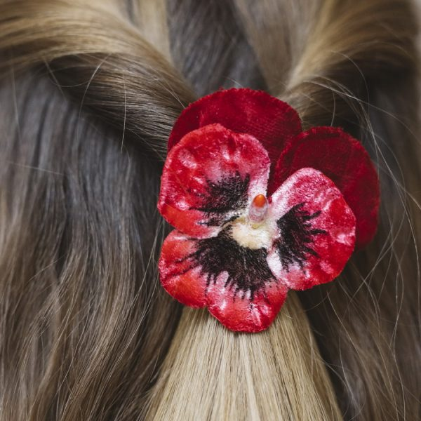 Detail image of Red Large Pansy Flower Hair Clip worn with a twisted hair style
