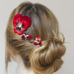 Red Pansy Hair Clip Gift Set worn with a classic bun hair style