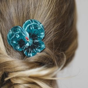 Detail image of Teal Pansy Flower Hair Clip worn with a ponytail