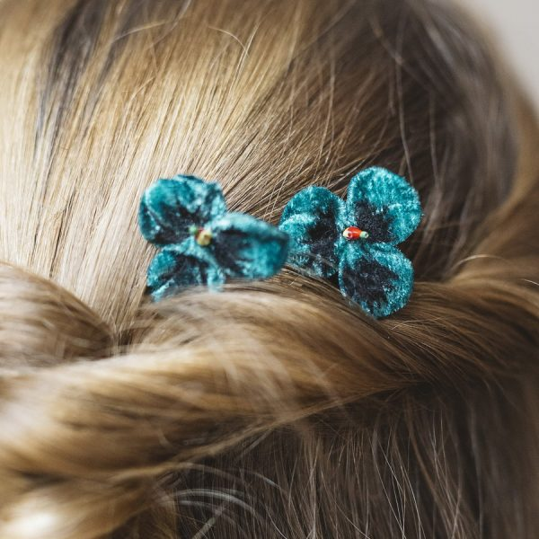 Detail image of Teal Pansy Flower Hair Clips worn with a twist ponytail